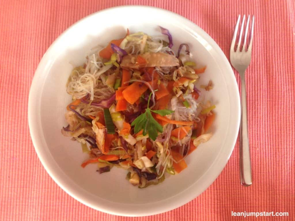 Chinese vegetable stir fry arranged on a white plate with fork on an orange table set.