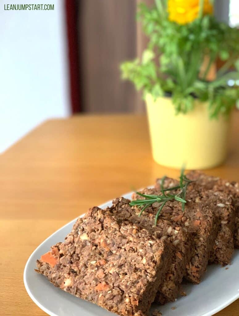 several lentil loaf slices with a yellow flower in the background