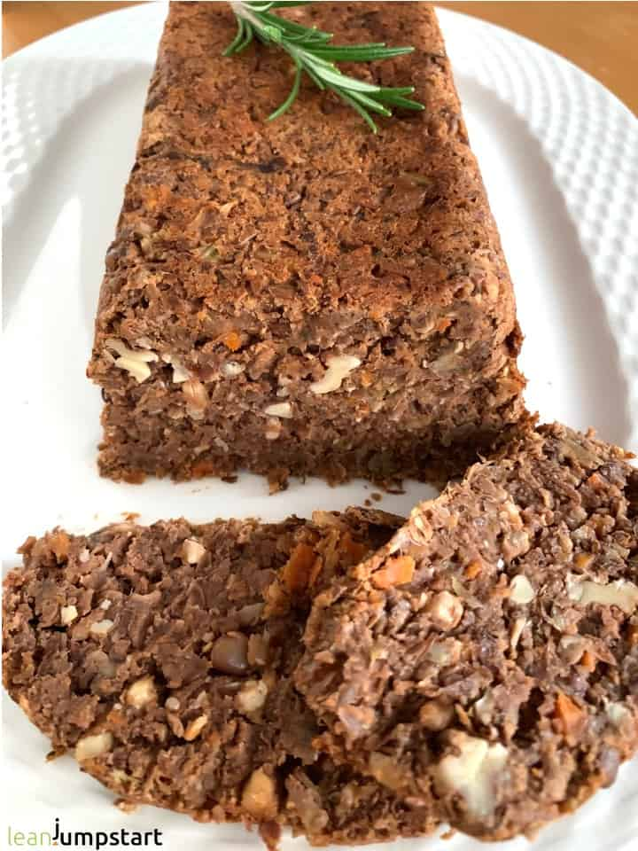 whole vegan lentil loaf with two slices in front