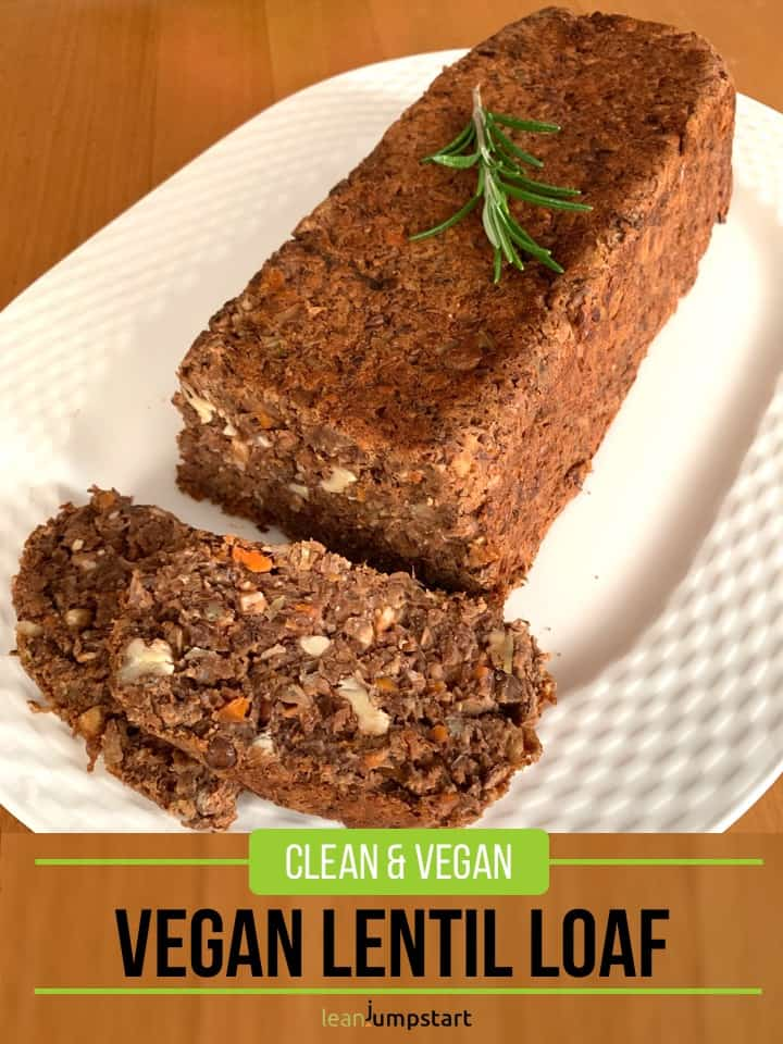 whole vegan lentil loaf on a large oval plate with slices cut and a rosemary stalk