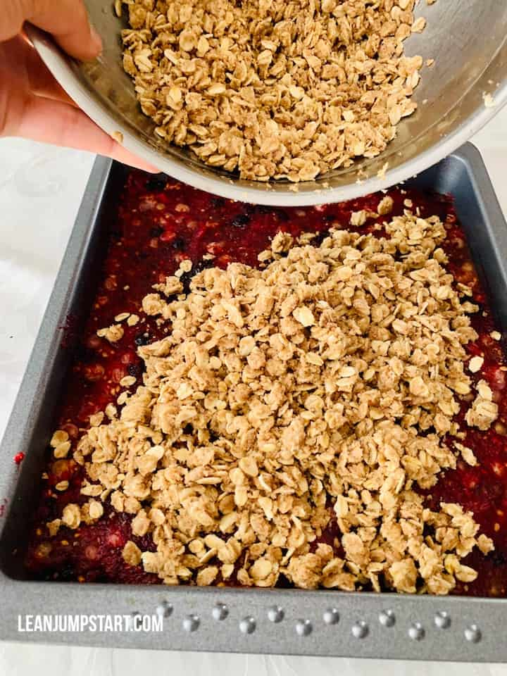 adding oat crumble topping on fruit layer